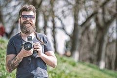 Conceito do fotógrafo Câmera farpada do vintage da posse do fotógrafo do moderno do homem Fotógrafo com o amador da barba e do bi fotos de stock