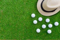 Conceito do golfe: Chapéu de Panamá, bolas de golfe, configuração lisa no vidro verde, Imagens de Stock