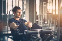Conceito do Gym, aptidão, esporte, saudável, estilo de vida O homem novo cabido senta-se levanta na máquina no sportswear fotos de stock royalty free