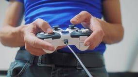 Conceito do homem que joga o console video das mãos do gamepad na tevê A mão guarda o manche novo que joga o console video na tev video estoque