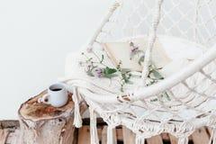 Conceito do hygge do verão com a cadeira da rede no jardim Imagem de Stock Royalty Free