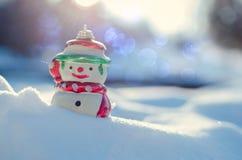 Conceito do inverno com o boneco de neve no fundo da neve Imagens de Stock