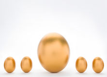 Conceito do investimento com os grandes e ovos dourados pequenos Imagens de Stock Royalty Free