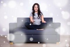 Conceito do lazer do inverno - mulher que olha a tevê em casa Fotografia de Stock Royalty Free