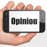 Conceito do mercado: Mão que guarda Smartphone com opinião na exposição Fotografia de Stock Royalty Free