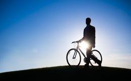 Conceito do monte de Holding Bicycle Silhouette do homem de negócios imagens de stock