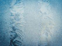 Conceito do mundo de fantasia da estação de feriados do inverno: Imagem macro de testes padrões azuis de Frosty Window Glass Natu imagens de stock