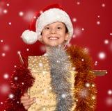 Conceito do Natal do feriado de inverno - menino no chapéu de Santa com dourado Fotografia de Stock Royalty Free