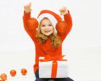 Conceito do Natal e dos povos - menina feliz no chapéu do inverno Fotografia de Stock