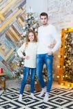 Conceito do Natal, forma pai e filha no pulôver elegante que levanta nos apartamentos luxuosos decorados para Fotos de Stock