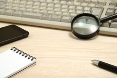 Conceito do negócio Almofada de memorando, telefone esperto, e lupa com teclado de computador Foto de Stock Royalty Free