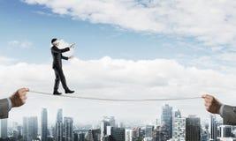 Conceito do negócio do apoio e do auxílio do risco com o homem que equilibra na corda Imagem de Stock Royalty Free