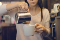 Conceito do negócio do café - barista da senhora do close-up no leite de preparação e de derramamento do avental imagem de stock