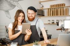 Conceito do negócio do café - satisfeito e os pares dos proprietários do sorriso olham em ordens da tabuleta em linha na cafetari foto de stock