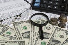 Conceito do negócio Close up dos espetáculos, das notas de dólar, da calculadora, da lupa e das moedas no papel com dígitos imagens de stock