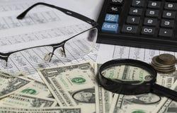 Conceito do negócio Close up dos espetáculos, das notas de dólar, da calculadora, da lupa e das moedas no papel com dígitos imagens de stock royalty free