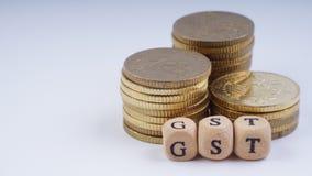 Conceito do negócio com uma palavra de GST em moedas empilhadas Fotografia de Stock Royalty Free