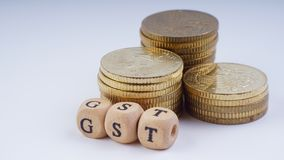 Conceito do negócio com uma palavra de GST em moedas empilhadas Fotos de Stock Royalty Free
