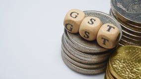 Conceito do negócio com uma palavra de GST em moedas empilhadas Foto de Stock Royalty Free