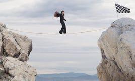 Conceito do negócio da mulher de negócios que supera os problemas que alcançam a bandeira em uma corda imagem de stock