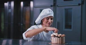 Conceito do negócio da padaria em uma senhora feliz carismática do padeiro da cozinha comercial que prova o creme do bolo com ded video estoque