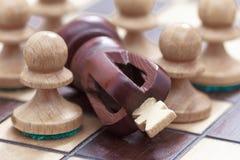 Conceito do negócio da vitória ou da derrota, do tabuleiro de xadrez da perda e das figuras do rei e dos penhores imagem de stock royalty free