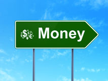 Conceito do negócio: Dinheiro e símbolo da finança no fundo do sinal de estrada Imagens de Stock