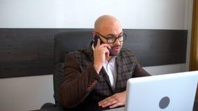 Conceito do negócio, dos povos, da comunicação e da tecnologia - homem de negócios de sorriso com chamar do laptop e dos papéis filme