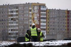 Conceito do negócio, dos trabalhos de equipa e dos povos - grupo de construtores de sorriso capacetes Web site Construtor-Rússia  imagem de stock