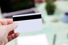 Conceito do negócio e da finança Entregue a posse cartões de crédito vazio com fundo de madeira do escritório da tabela Foto de Stock