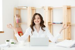 Conceito do negócio e da saúde: Jovem mulher perto do portátil, meditação praticando do retrato na mesa de escritório, na frente  fotografia de stock royalty free