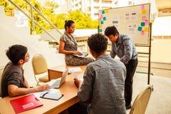 Conceito do negócio e dos trabalhos de equipa: Homens de negócios e sessão de reflexão da mulher na reunião da conferência do pla fotografia de stock