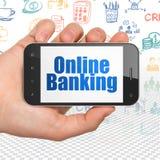 Conceito do negócio: Entregue guardar Smartphone com operação bancária em linha na exposição Foto de Stock Royalty Free