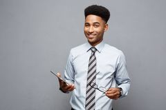 Conceito do negócio - homem de negócios afro-americano profissional considerável feliz que guarda a tabuleta digital e a conversa foto de stock