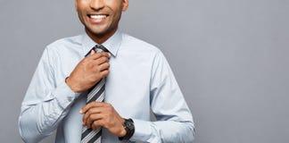 Conceito do negócio - homem de negócios afro-americano profissional seguro feliz que levanta sobre o fundo cinzento foto de stock royalty free
