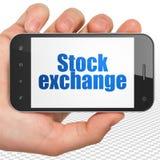 Conceito do negócio: Mão que guarda Smartphone com a bolsa de valores na exposição Imagem de Stock