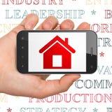 Conceito do negócio: Mão que guarda Smartphone com casa na exposição Imagens de Stock