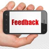 Conceito do negócio: Mão que guarda Smartphone com feedback na exposição Imagens de Stock Royalty Free