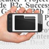 Conceito do negócio: Mão que guarda Smartphone com o dobrador na exposição Foto de Stock