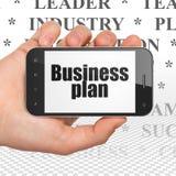 Conceito do negócio: Mão que guarda Smartphone com plano de negócios na exposição Imagem de Stock Royalty Free