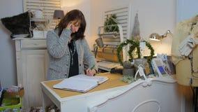 Conceito do negócio - mulher de negócios que fala no telefone e nas notas video estoque
