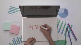 Conceito do negócio A mulher escreve o PLANEAMENTO no papel no portátil Desktop do escritório filme