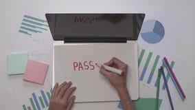Conceito do negócio A mulher escreve a SENHA no papel no portátil Desktop do escritório vídeos de arquivo