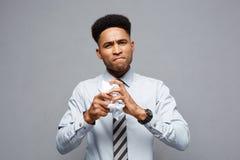 Conceito do negócio - retrato do homem de negócios afro-americano sério que guarda o amarrotamento de papéis do relatório nas mão Foto de Stock