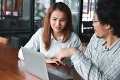 Conceito do negócio do trabalho da equipe Empresários asiáticos novos que trabalham com portátil junto no local de trabalho no es imagens de stock royalty free
