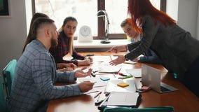 Conceito do negócio Uma equipe de trabalho na conferência Uma mulher tira algo no papel e no aplauso da equipe seus vídeos de arquivo