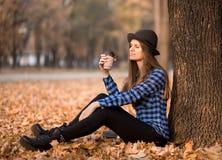 Conceito do outono, mulher que aprecia o copo de café afastado no dia ensolarado da queda imagem de stock