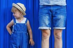 Conceito do pai e da filha Estão de lado a lado em um b azul imagens de stock royalty free