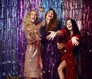 Conceito do partido e dos feriados Tr?s mulheres do encanto em lantejoulas luxuosas do brilho vestem ter o divertimento fotografia de stock