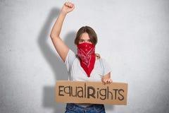 Conceito do protesto das mulheres A fêmea europeia nova séria com o bandana na cara, placa das posses com inscrição, levanta a mã imagem de stock royalty free